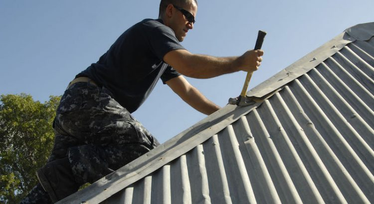 A roofing contractor repairing a damaged roof